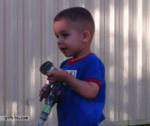 ребенок пробует поймать воду из водяного шланга
